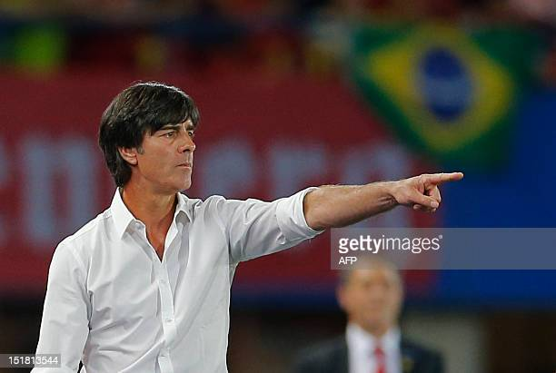 Germany's national football team head coach Joachim Low gestures as a Brazilian flag is seen in the background during a 2014 World Cup qualification...