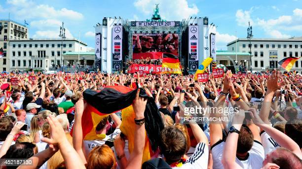 Germany's national football team playes and team members are displayed on a giant screen as hundreds of thousands of football fans gather at the...