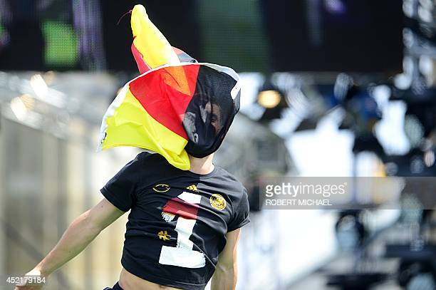 Germany's national football team's goalkeeper Manuel Neuer has his face covered with a national flag as he celebrates their FIFA World Cup 2014 title...