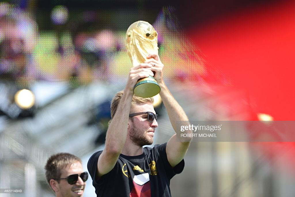 Germany's national football team's midfielder Christoph Kramer (R) holds the trophy in front of fans next to defender Philipp Lahm as they arrive on a stage installed for a victory parade on July 15, 2014 at Berlin's landmark Brandenburg Gate to celebrate their FIFA World Cup 2014 title. Germany won their fourth World Cup title, after 1-0 win over Argentina on July 13, 2014 in Rio de Janeiro in the FIFA World Cup Brazil final game. MICHAEL