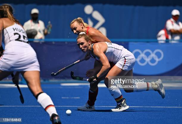 Germany's Nike Lorenz is marked by Britain's Hannah Martin during their women's pool A match of the Tokyo 2020 Olympic Games field hockey...