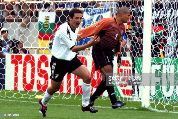 Germany's Oliver Neuville celebrates scoring Germany's winning goal against Paraguay as goalkeeper Jose Luis Chilavert looks back dejected