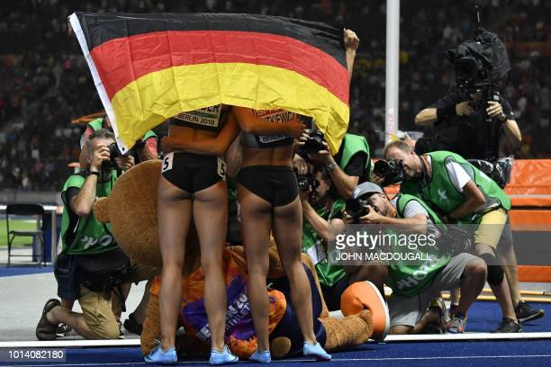 Germany's Pamela Dutkiewicz and Germany's Cindy Roleder pose for photographers with their national flag after the women's 100m Hurdles final race...