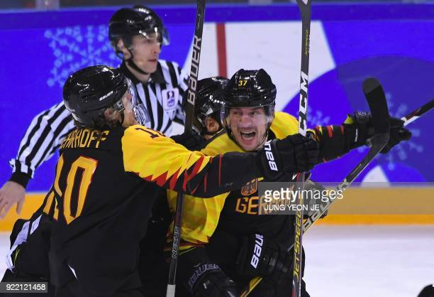 TOPSHOT Germany's Patrick Reimer celebrates with teammates after scoring the winning goal in overtime of the men's quarterfinal ice hockey match...