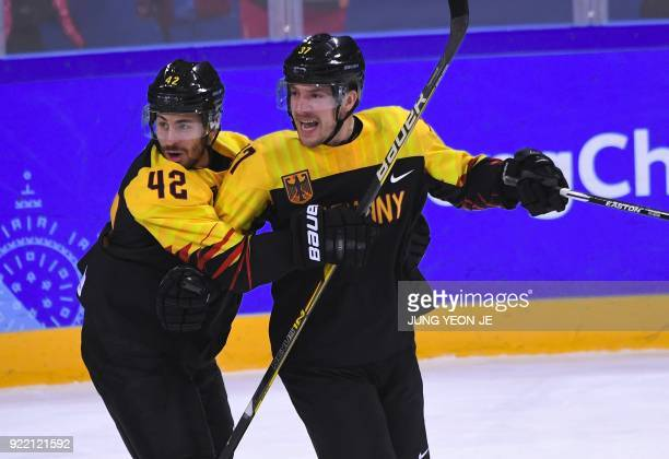 Germany's Patrick Reimer celebrates with teammates after scoring the winning goal in overtime of the men's quarterfinal ice hockey match between...