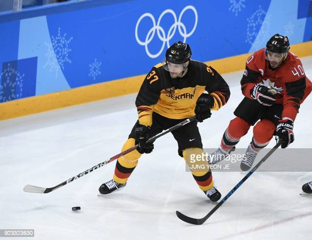 Germany's Patrick Reimer tries to get past Canada's Maxim Lapierre in the men's semifinal ice hockey match between Canada and Germany during the...