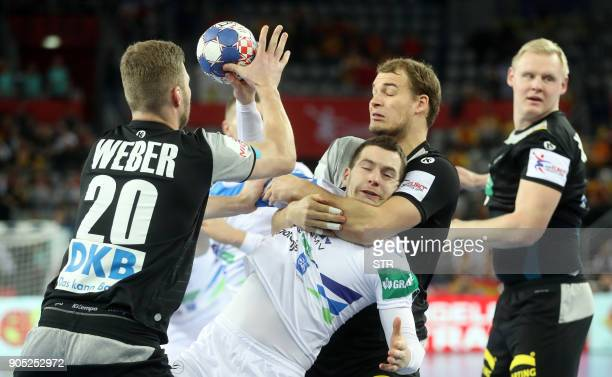 Germany's Paul Drux and Philipp Weber vies with Slovenia's Marko Bezjak during the preliminary round group C match of the Men's 2018 EHF European...
