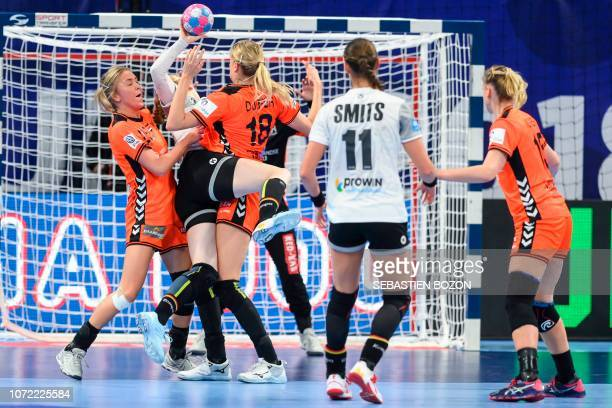 Germany's pivot Meike Schmelzer vies for the ball with Netherlands' right back Charris Rozemalen and Netherlands' left back Kelly Dulfer during the...