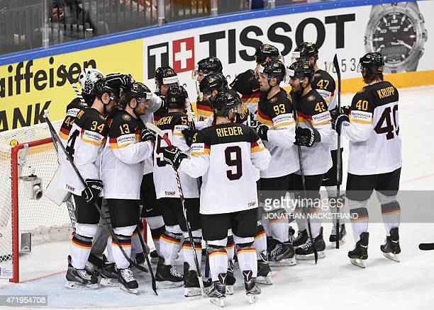Germany's players celebrate after winning the group A preliminary round match France vs Germany at the 2015 IIHF Ice Hockey World Championships on...
