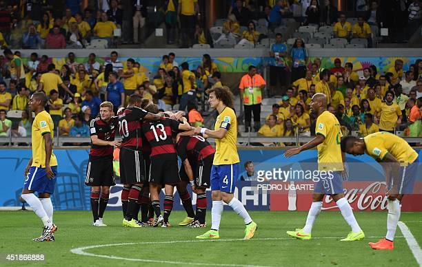 Germany's players celebrate scoring a goal as Brazilian players react during the semifinal football match between Brazil and Germany at The Mineirao...