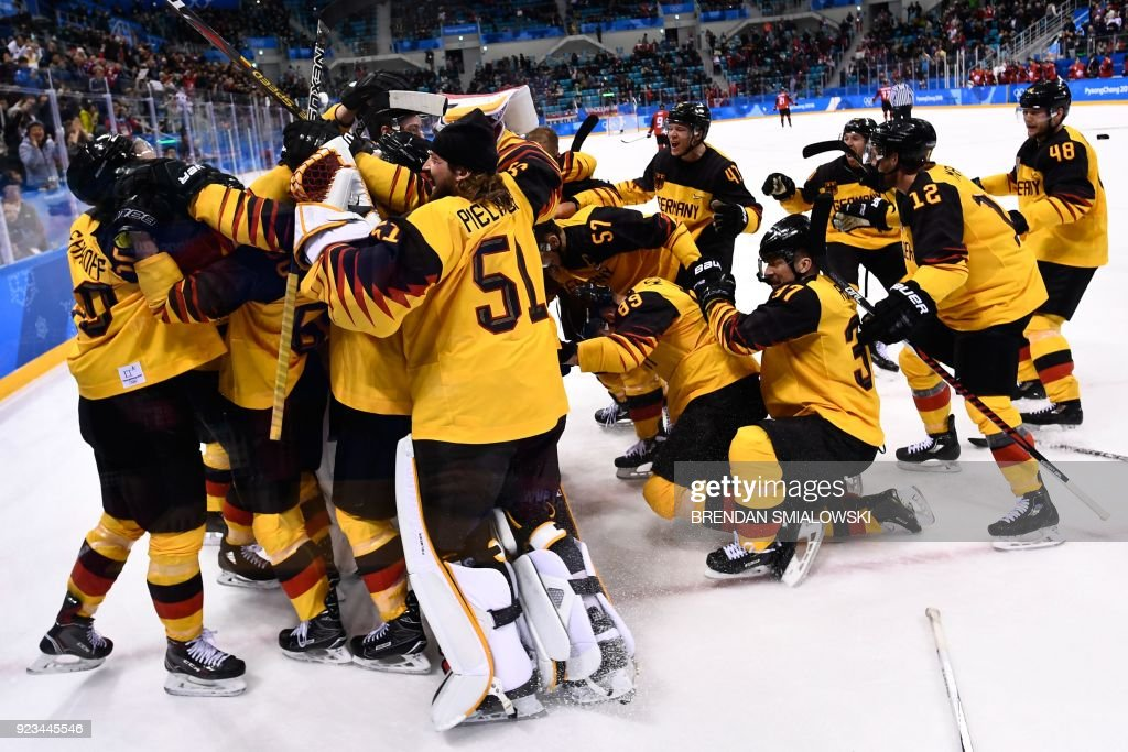 TOPSHOT - Germany's players celebrate winning the men's semi-final ice hockey match between Canada and Germany during the Pyeongchang 2018 Winter Olympic Games at the Gangneung Hockey Centre in Gangneung on February 23, 2018. / AFP PHOTO / Brendan Smialowski