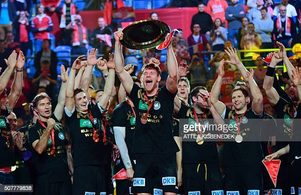 TOPSHOT Germany's players celebrate with the trophy after winning the final match of the Men's 2016 EHF European Handball Championship between...