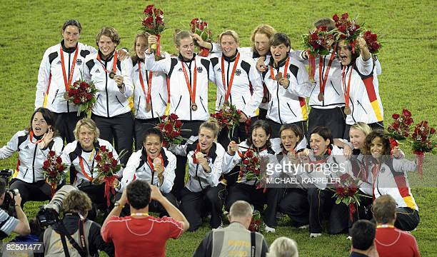 Germany's players celebrate with their bronze medals after beating Japan 2-0 in the women's football competition in the 2008 Beijing Olympic Games in...