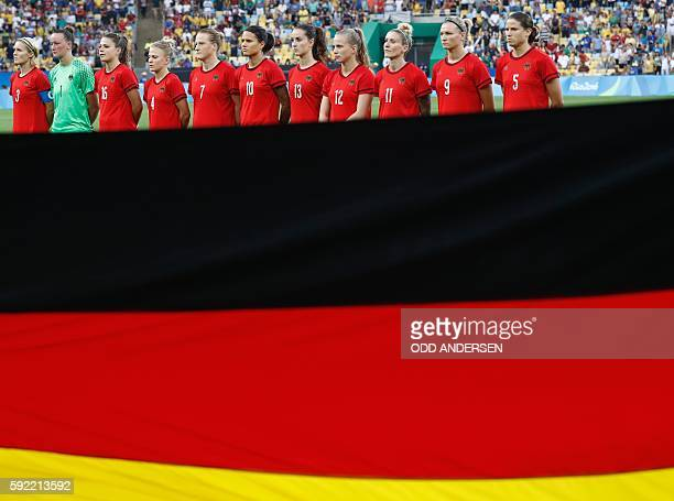 Germany's players listen to the national anthem prior to the Rio 2016 Olympic Games women's football Gold medal match at the Maracana stadium in Rio...