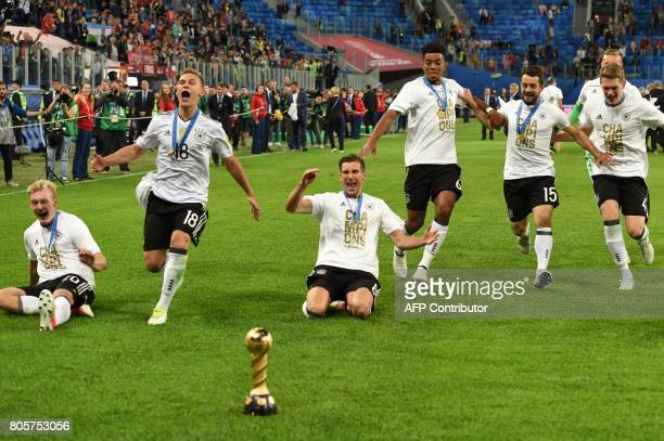Germany's players run towards the trophy as they celebrate winning the 2017 Confederations Cup final football match between Chile and Germany at the...