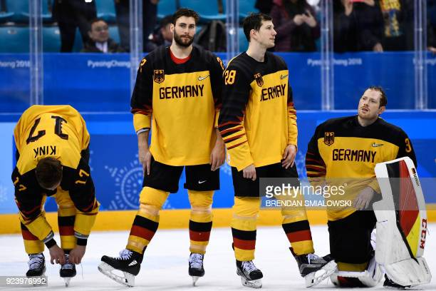 TOPSHOT Germany's players wait to receive their silver medals on the podium during the medal ceremony after the men's gold medal ice hockey match...