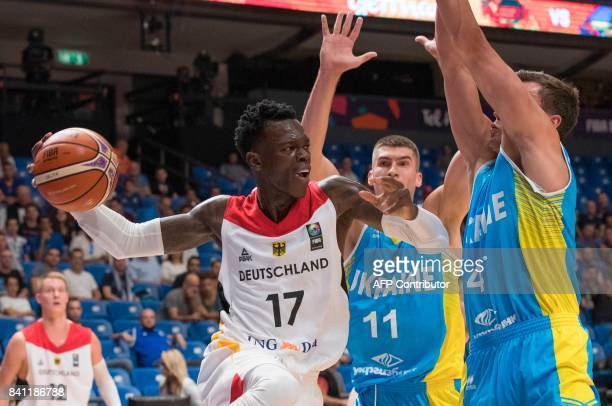 Germany's point guard Dennis Schroder attempts to pass as he is marked by Ukraine's small forward Maksym Pustozvonov and small forward Oleksandr...