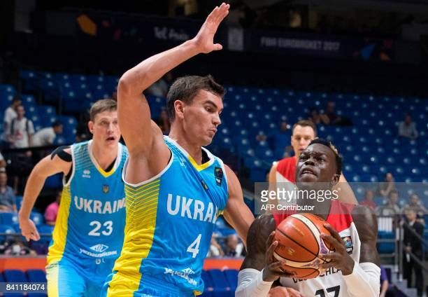 Germany's point guard Dennis Schroder dribbles as he is marked by Ukraine's small forward Maksym Pustozvonov during the FIBA EuroBasket 2017...