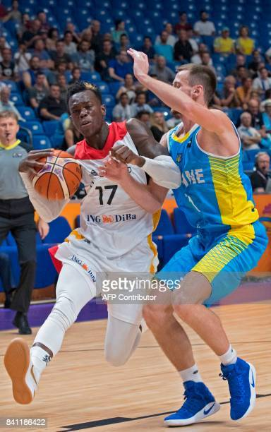 Germany's point guard Dennis Schroder dribbles as he is marked by Ukraine's shooting guard Olexandr Mishula during the FIBA EuroBasket 2017...
