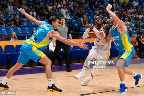 Germany's point guard Dennis Schroder dribbles as he is marked by Ukraine's shooting guard Olexandr Mishula and small forward Maksym Pustozvonov...
