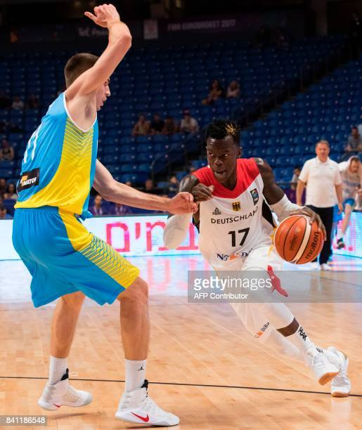 Germany's point guard Dennis Schroder dribbles as he is marked by Ukraine's small forward Oleksandr Lypovyy during the FIBA EuroBasket 2017...
