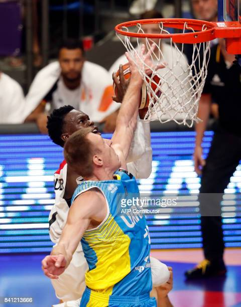 Germany's point guard Dennis Schroder drives to the basket as he is marked by Ukraine's power forward Maksym Korniyenko during the FIBA EuroBasket...