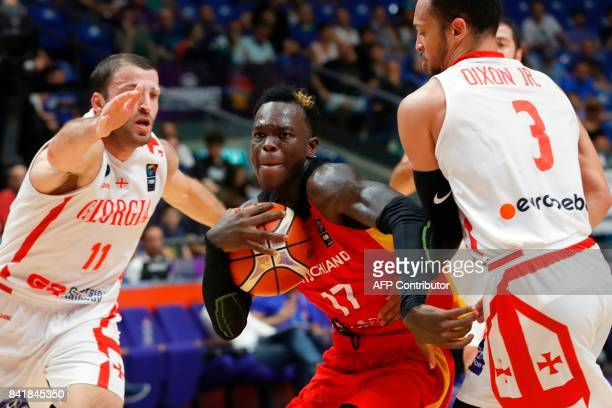Germany's point guard Dennis Schroder vies for the ball with Georgia's guard Michael Dixon Jr and point guard George Tsintsadze during their FIBA...