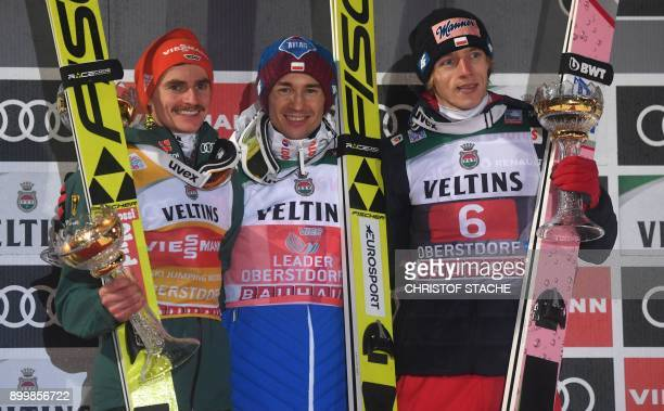 Germany's Richard Freitag Poland's Kamil Stoch and Poland's Dawid Kubacki pose on the podium after the ski jumping event in Oberstdorf southern...