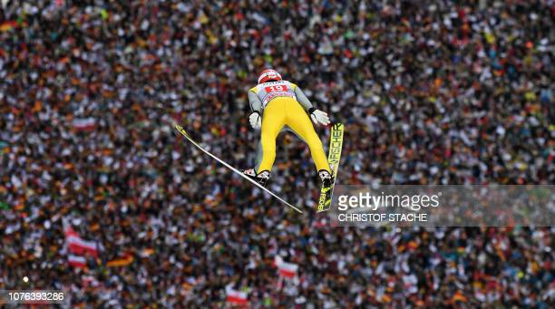 TOPSHOT Germany's Richard Freitag soars over spectators during his first competition jump at the second stage of the FourHills Ski Jumping tournament...