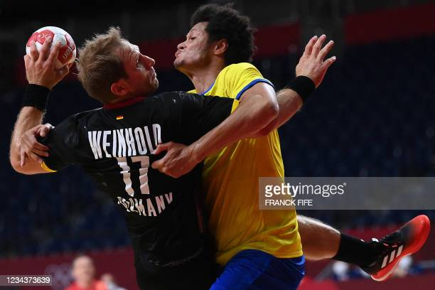 Germany's right back Steffen Weinhold is challenged by Brazil's left back Thiagus Petrus during the men's preliminary round group A handball match...