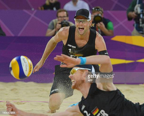 Germany's right blocker Jonas Reckermann dives to reach the ball as teammate Julius Brink looks on during the men's beach volleyball final match on...