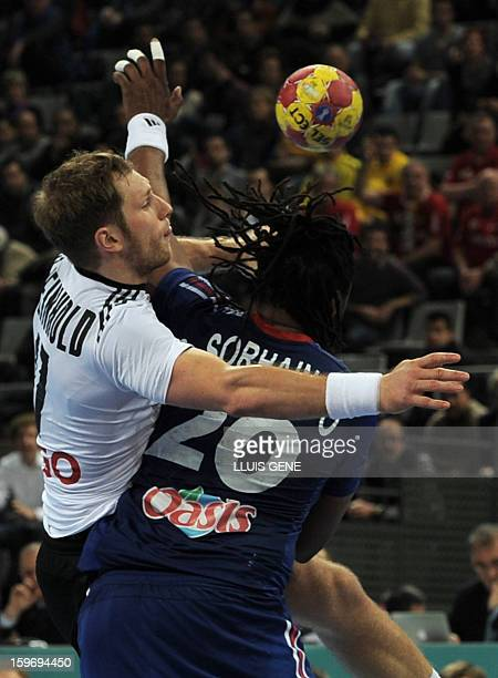 Germany's right wing Steffen Weinhold vies with France's pivot Cedric Sorhaindo during the 23rd Men's Handball World Championships preliminary round...