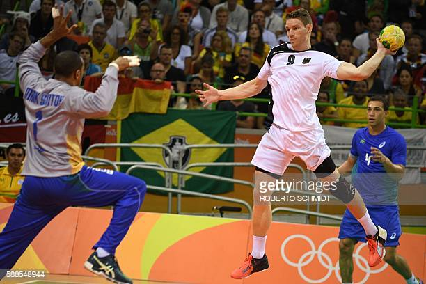 Germany's right wing Tobias Reichmann jumps to shoot at Brazil's goalkeeper Maik dos Santos during the men's preliminaries Group B handball match...