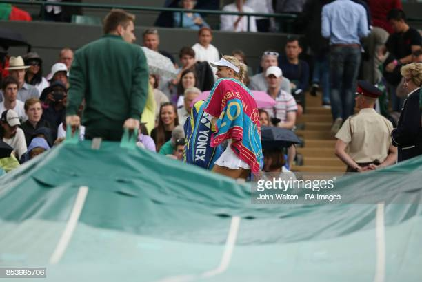 Germany's Sabine Lisicki leaves the court as rain delays her match against Serbia's Ana Ivanovic during day eight of the Wimbledon Championships at...