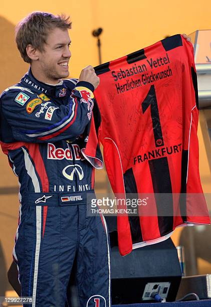 Germany's Sebastian Vettel holds up a jersey of German second division soccer team Eintracht Frankfurt which he got a a gift after driving his 'Kinky...