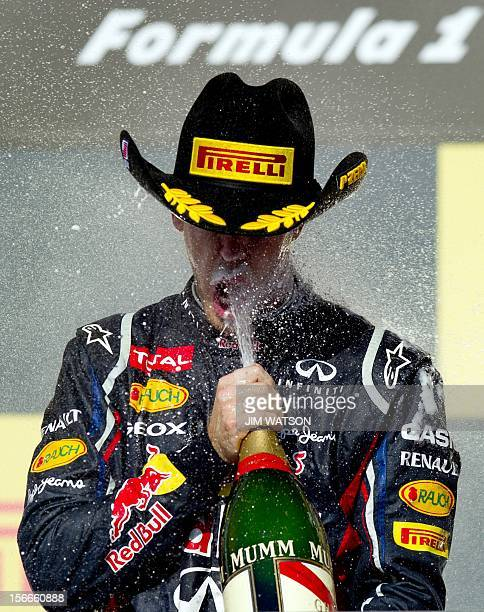 Germany's Sebastian Vettel of Red Bull Racing drinks champagne after finishing second in the United States Formula One Grand Prix at the Circuit of...