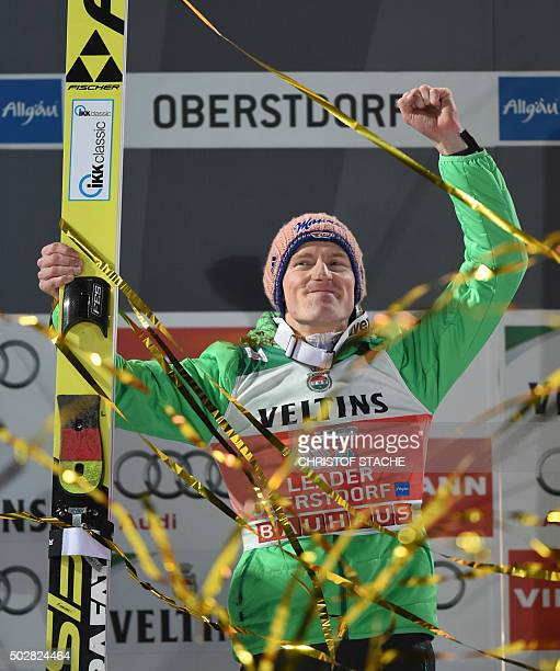Germany's Severin Freund celebrates on the podium after winning the ski jumping event in Oberstdorf southern Germany which is the first station of...