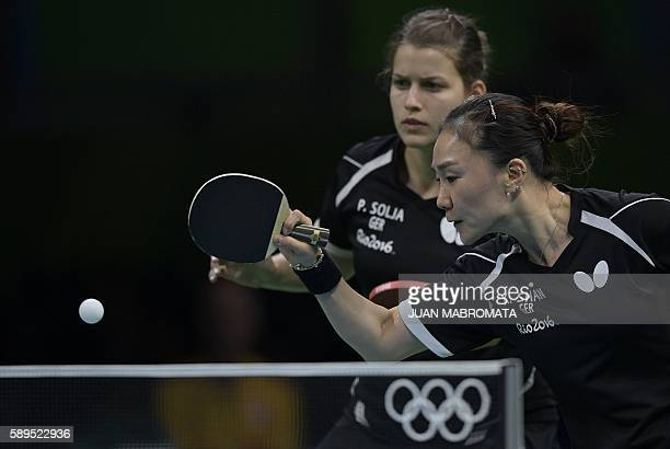 Germany's Shan Xiaona hits a shot next to Germany's Petrissa Solja in the women's team semi-final table tennis match against Japan's Mima Ito and...