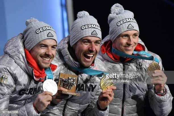 Germany's silver medallist Fabian Riessle, Germany's gold medallist Johannes Rydzek and Germany's bronze medallist Eric Frenzel pose on the podium...