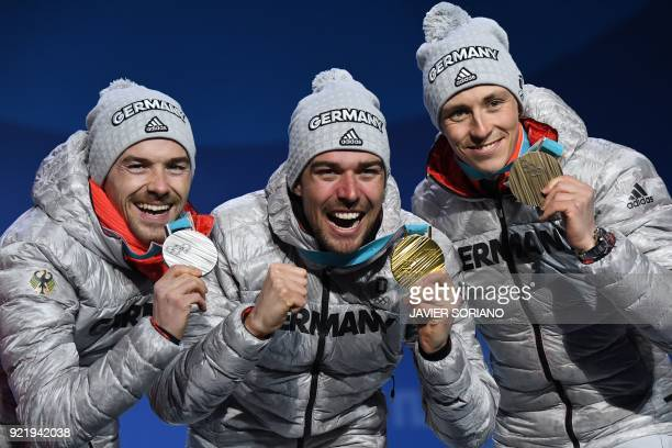 TOPSHOT Germany's silver medallist Fabian Riessle Germany's gold medallist Johannes Rydzek and Germany's bronze medallist Eric Frenzel pose on the...