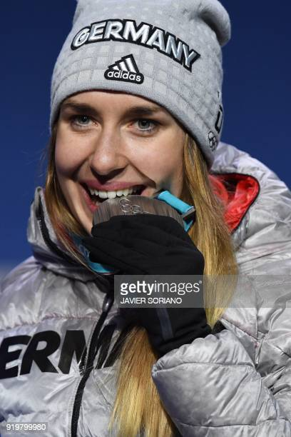 Germany's silver medallist Jacqueline Loelling bites her medal on the podium during the medal ceremony for the women's skeleton at the Pyeongchang...
