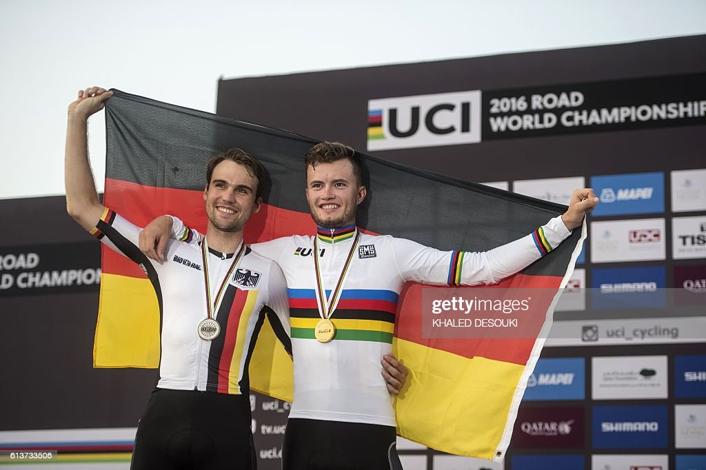 Germany's silver medallist Maximilian Schachmann (L) and gold medallist Marco Mathis celebrate on the podium at the end of the men's under 23 individual time trial event as part of the 2016 UCI Road World Championships on October 10, 2016, in the Qatari capital Doha. / AFP / KHALED