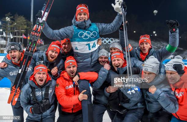Germany's silver medallist Simon Schempp celebrates with teammates after the Men's Biathlon 15 km Mass Start race during the PyeongChang 2018 Winter...