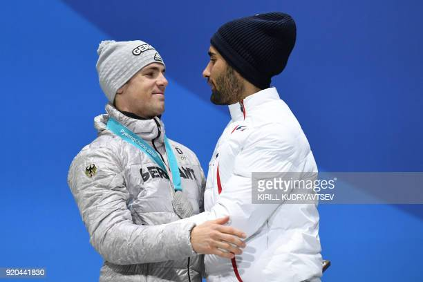 TOPSHOT Germany's silver medallist Simon Schempp hugs France's gold medallist Martin Fourcade on the podium during the medal ceremony for the...