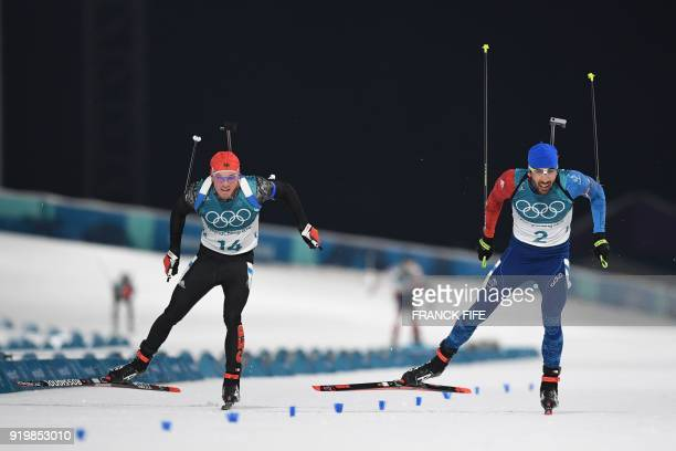 TOPSHOT Germany's Simon Schempp and France's Martin Fourcade cross the finish line to win silver and gold in the men's 15km mass start biathlon event...