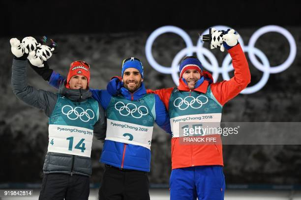 TOPSHOT Germany's Simon Schempp France's Martin Fourcade and Norway's Emil Hegle Svendsen celebrate on the podium during the victory ceremony in the...