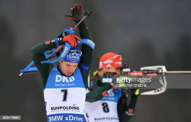 Germany's Simon Schempp shoulders his gun beside his compatriot Arnd Peiffer during the warmup shooting prior the men's 15 kilometer mass start...