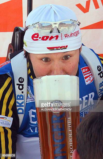 Germany's Simone Hauswald the winner of the women 125 km mass start event tastes a sponsor's alcoholfree beer on the podium of the ski stadium in the...