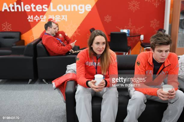 Germany's skeleton silver medallist Jacqueline Loelling and Germany's ski jumping large hill silver medallist Andreas Wellinger wait backstage at the...