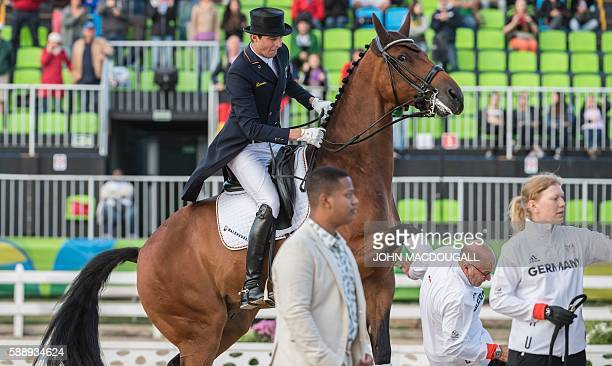 Germany's Sonke Rothenberg on Cosmo grimaces after his horse hit a groom cutting his head during the victory ceremony of the Equestrian's Dressage...